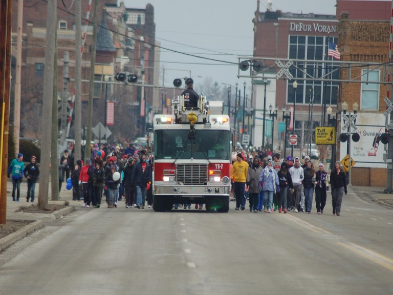 A firetruck leads walkers through town.